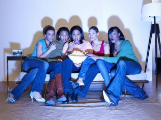 Five female friends watching television on couch in living room