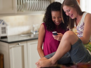 Two teenage girls with cell phone laughing