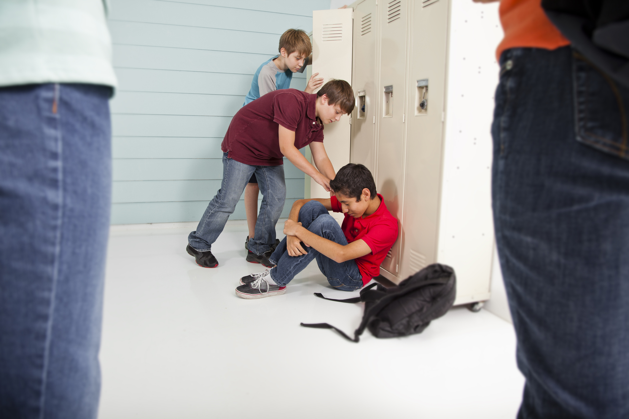 Teenage boys bully classmate in school hallway.
