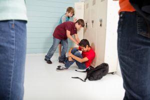 Teenage boys bully classmate in school hallway.
