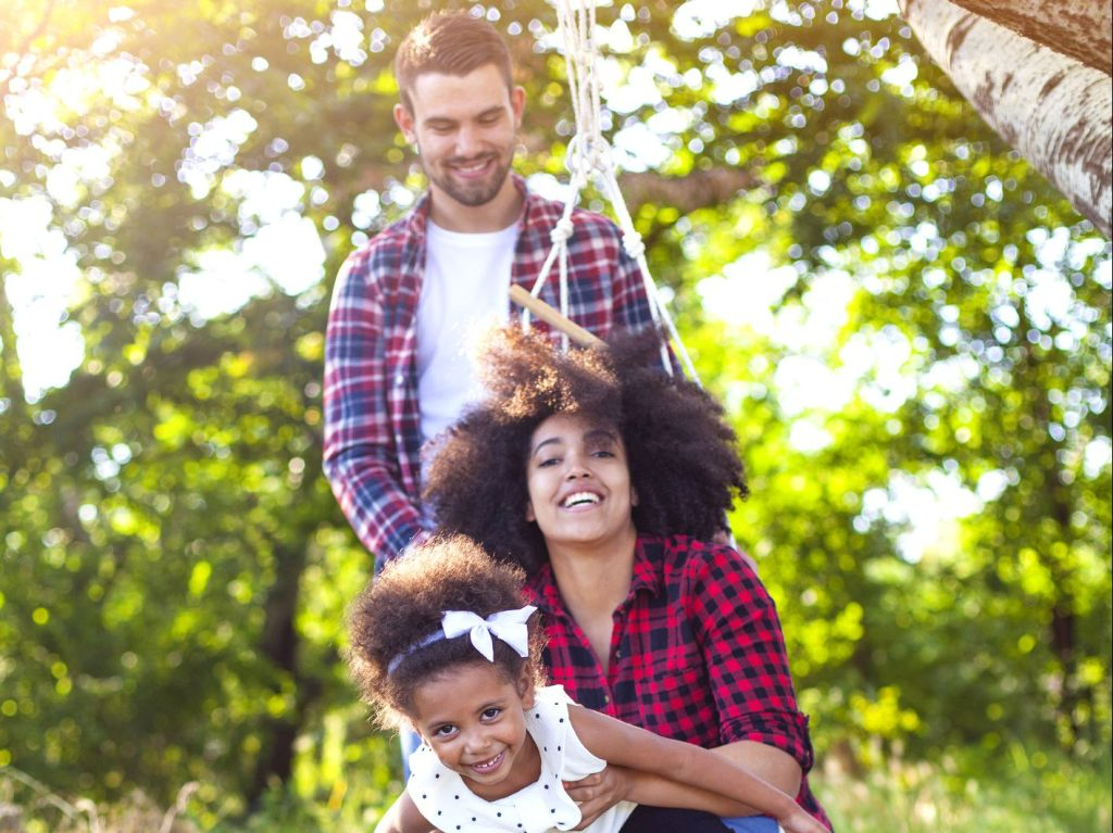 Happy family having fun with a swing in the forest