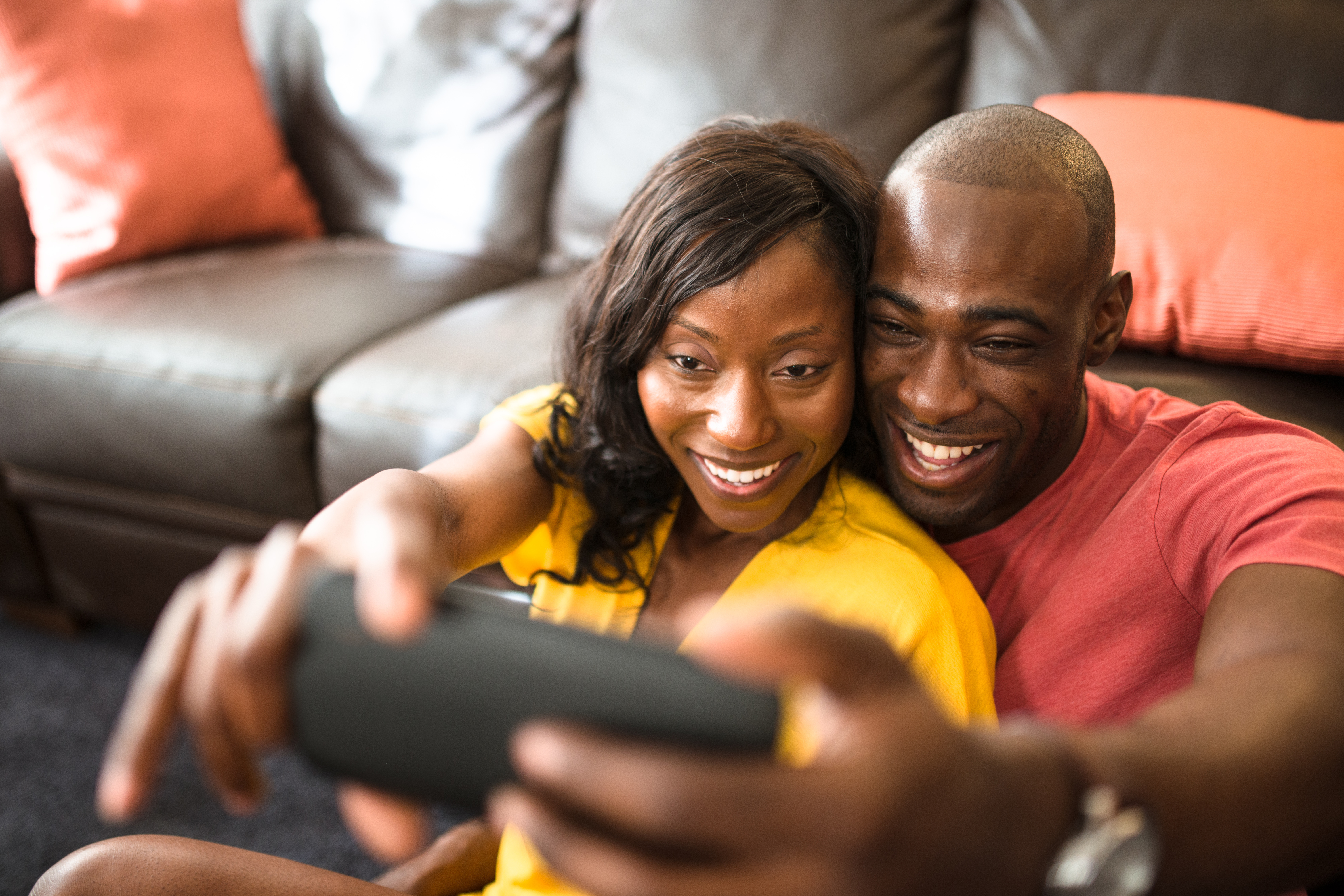 afro couple take a selfie on the couch
