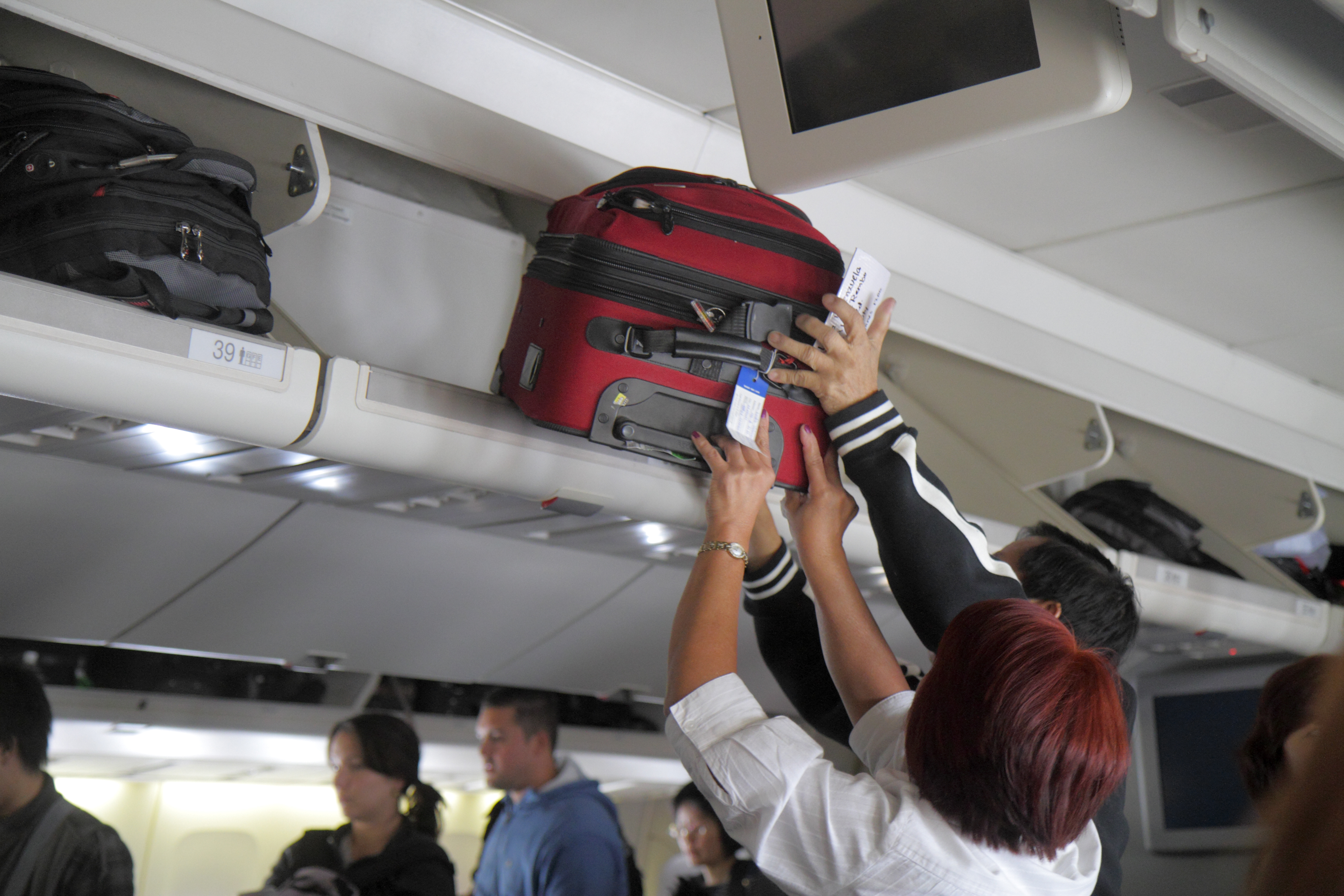 United commercial airliner cabin man woman overhead luggage bin suitcases