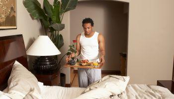 Man serving breakfast in bed to sleeping woman