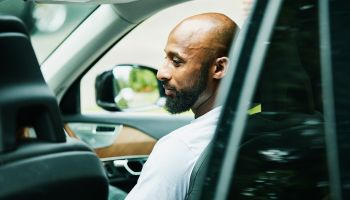 Smiling man seated in passenger seat of car waiting