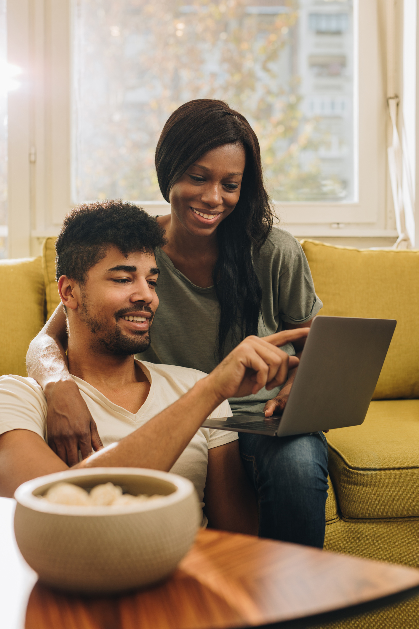 Happy African American couple surfing the net on laptop at home.