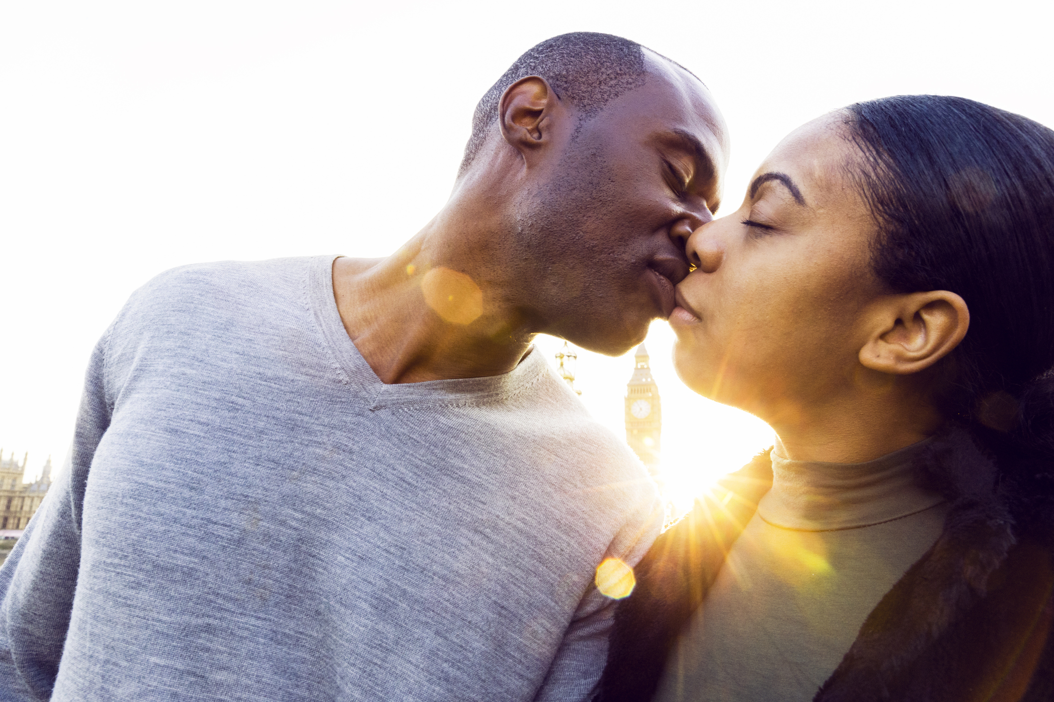 Couple kiss with the setting sun in the background
