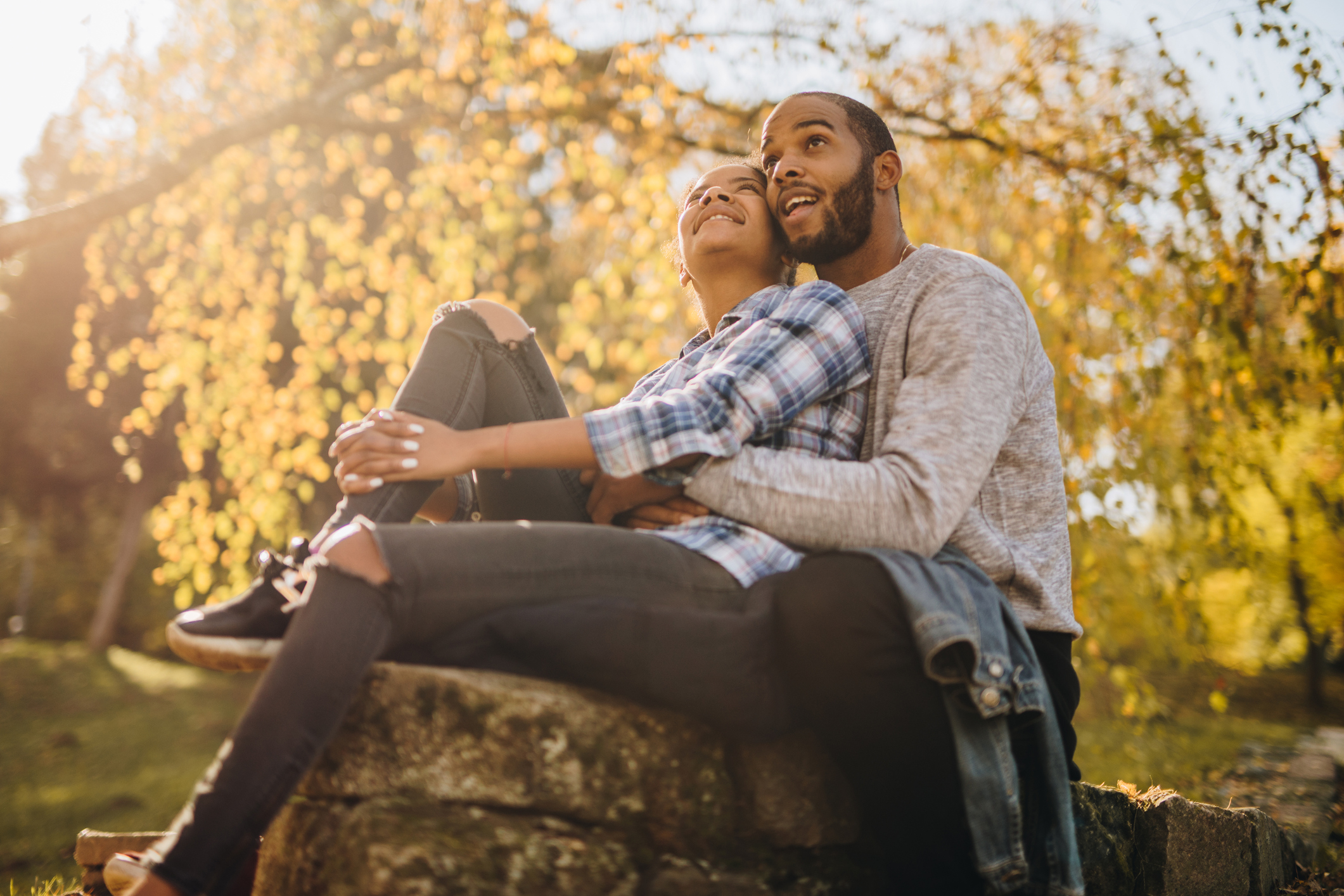 Happy embraced black couple enjoying in autumn day together.