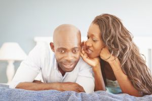 Whispering Secrets African Couple Lying in Bed