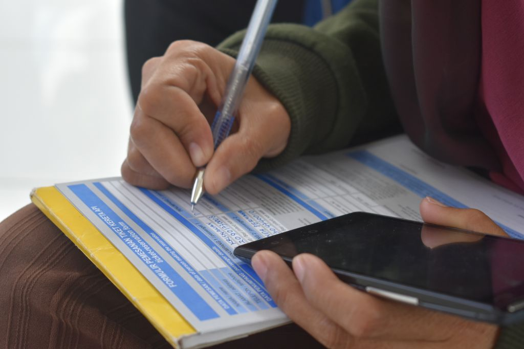 Midsection Of Person Holding Smart Phone Writing On Paper