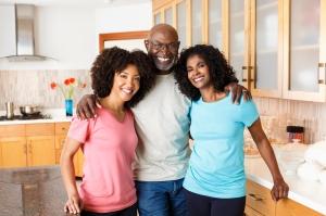 Black family hugging in kitchen