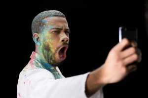 Man covered in powder paint taking selfie
