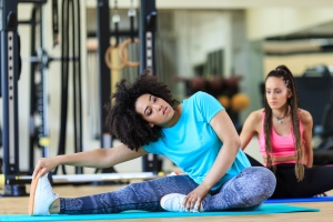 Women sitting on ground and stretching in gym