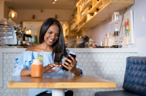 Black woman at a cafeteria drinking a smoothie and looking at her smartphone