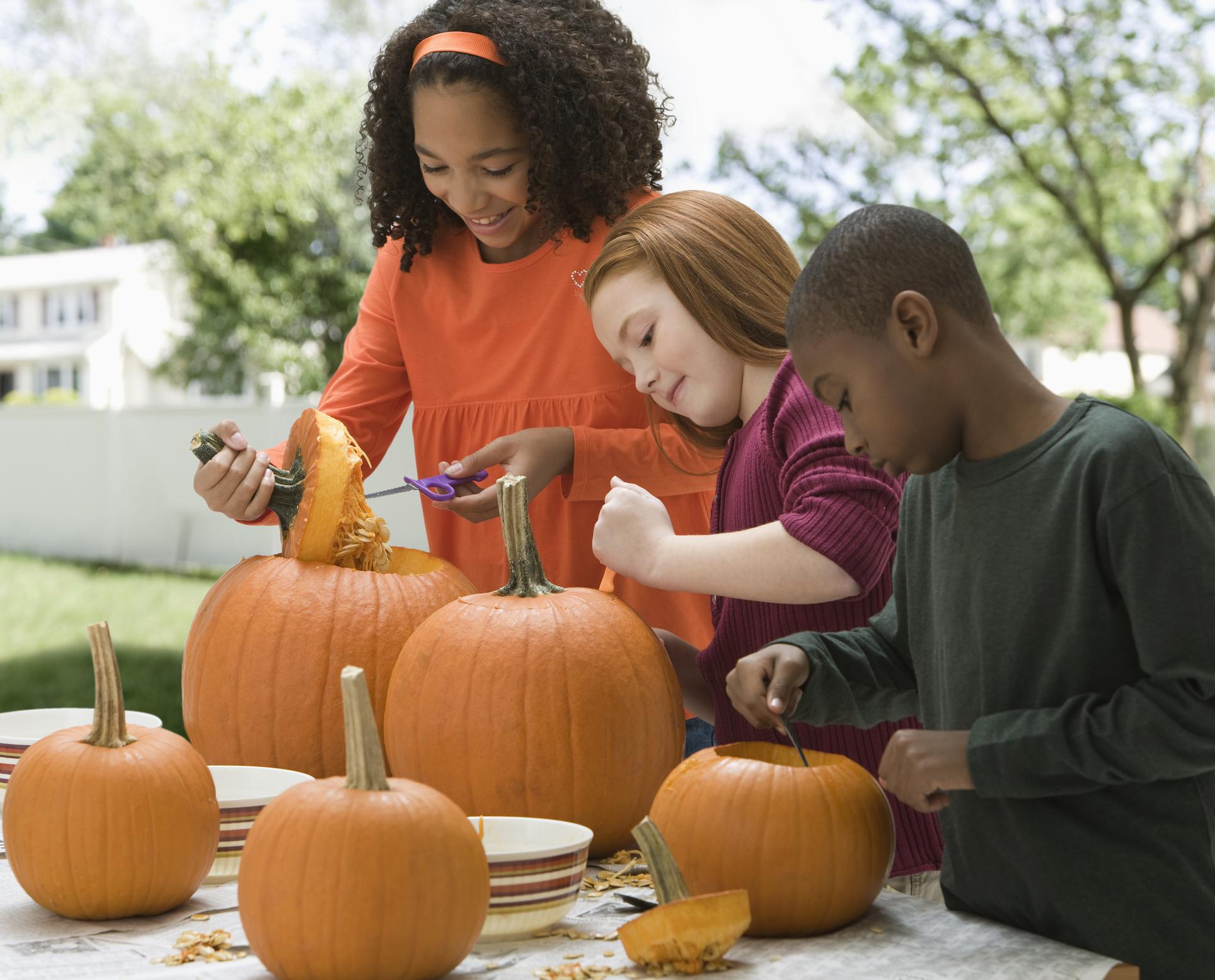 Children carving Halloween pumpkins together