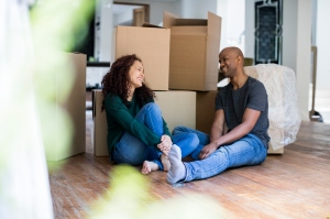 Smiling couple talking while relaxing in new home