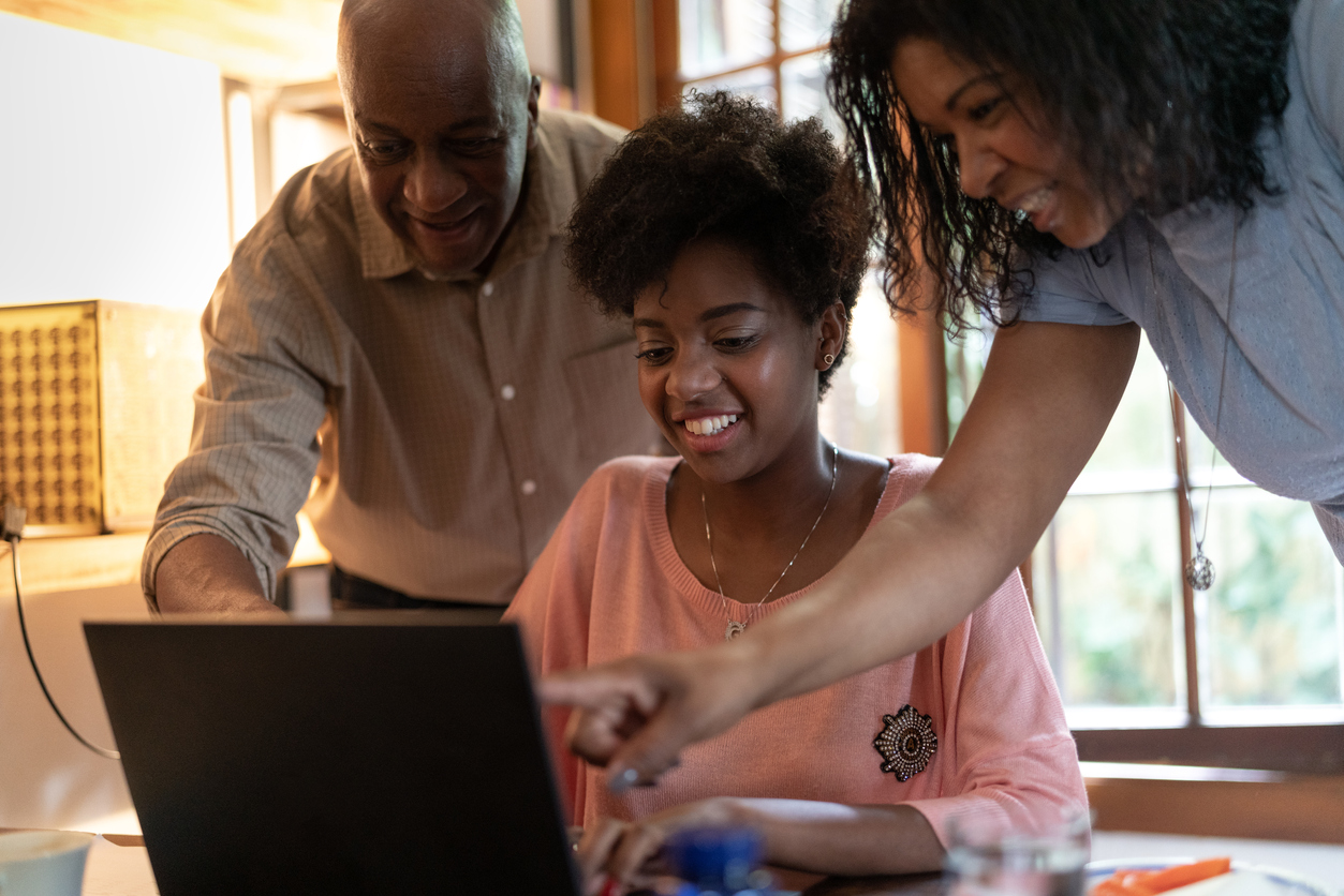 Parents helping daughter while using computer