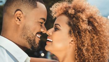 Afro couple kissing outdoors