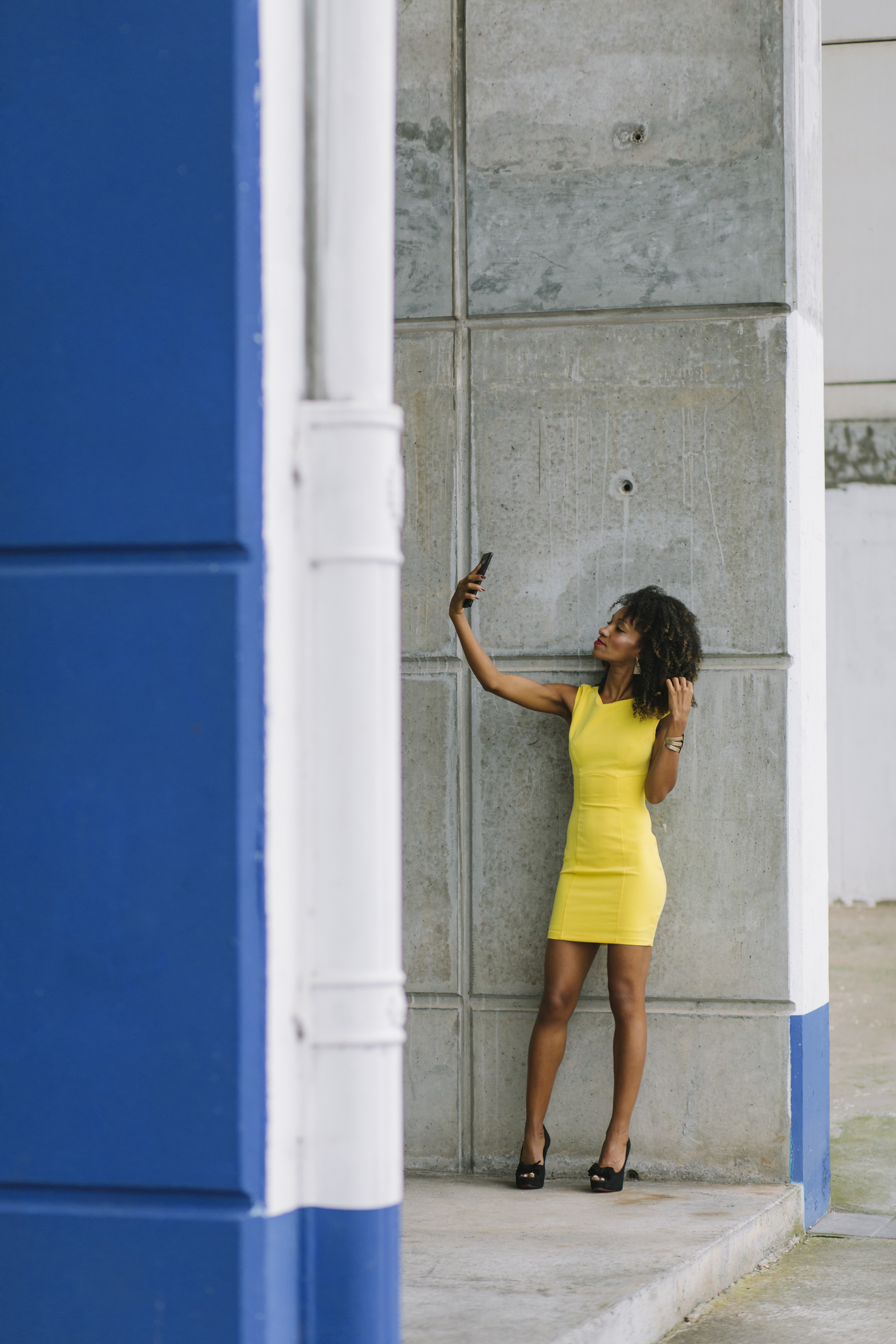 Fashionable businesswoman in yellow dress taking selfie with smartphone