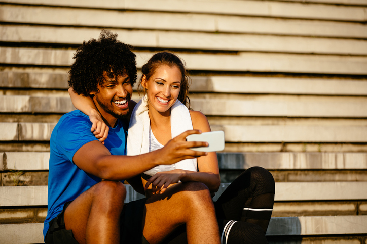 Young fit couple relaxing after workout and taking Selfie
