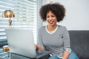 African American young woman using laptop in the living room