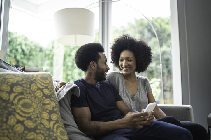 Afro couple using cellphone at home