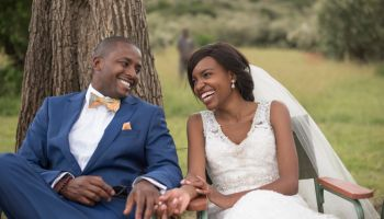 Close-Up of Smiling Bride and Groom Sitting on Chairs Holding Hands and Looking Adoringly into Each Other's Eyes