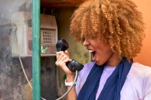 Woman yelling into old-fashioned telephone receiver