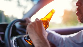 Drunk asian young man drives a car with a bottle of beer