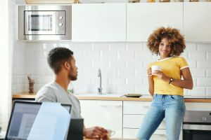 Young couple talking in kitchen at home