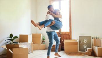 Happy young man carrying woman into new house