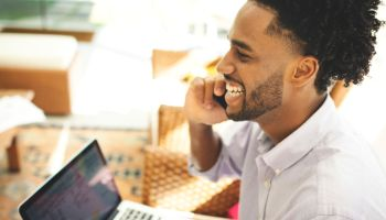 Young man using laptop, cell phone and credit card