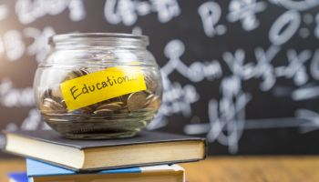 """Many money coin in the glass jar with 'Education"""" wording"""