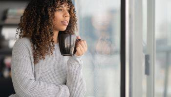 Portrait of a beautiful black woman drinking tea by window