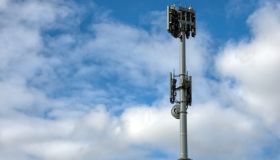 Mobile phone repeater tower against a cloudy blue sky