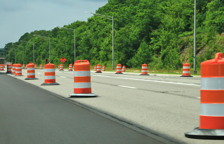 Orange construction barrels along the highway