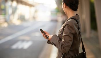 Businesswoman waiting on bus stop with smartphone