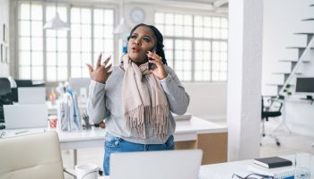African businesswoman talking on phone in modern office