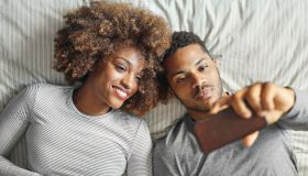 Smiling couple taking selfie while lying on in bed