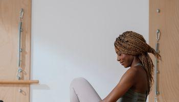 Sportswoman Sitting on Pilates Reformer