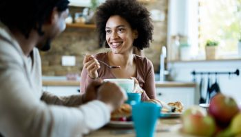 Happy black woman talking to her boyfriend during breakfast at home.