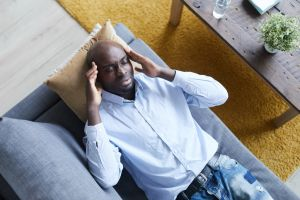 Above view of troubled young Afro-American man in shirt lying on psychiatrists couch and massaging temples at therapy session