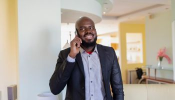 Self-Confident African Businessman at Home Using a Mobile Phone
