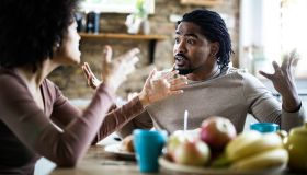 Angry African American man arguing with his girlfriend during breakfast in the morning.