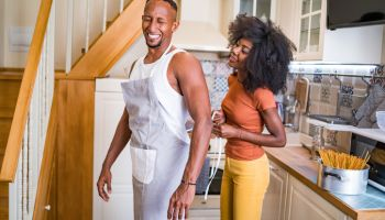 Happy couple in love cooking spaghetti at home