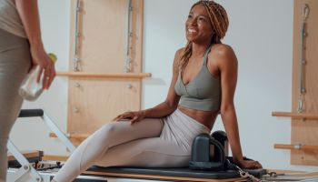 Beautiful African smiling sportswoman sitting on pilates reformer and chatting with her girlfriend.
