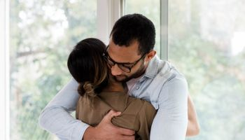 Mid adult husband gives unrecognizable military wife hug