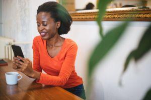 Beautiful woman using phone at cafe