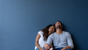 Thoughtful couple at home leaning against a wall and smiling