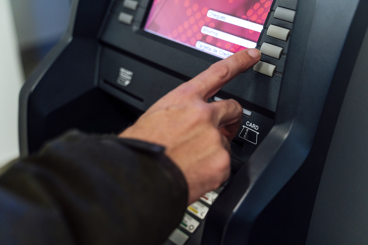 Man typing secret number from a bank ATM to withdraw money
